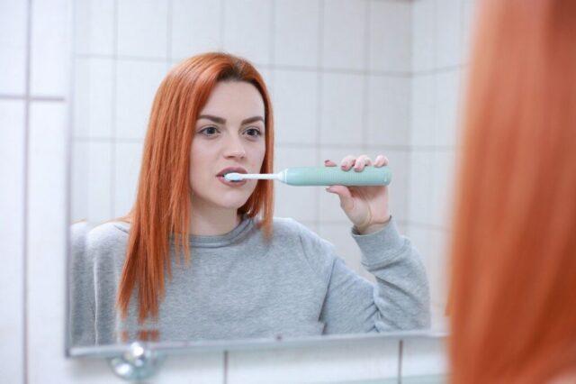 鏡を見て歯磨きしている女性