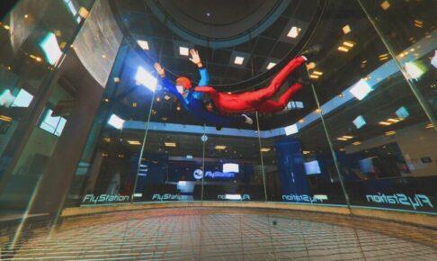 インドアスカイダイビングで宙を舞う男性